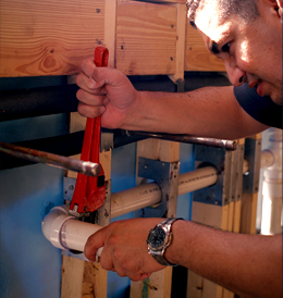 man installing piping in a wall