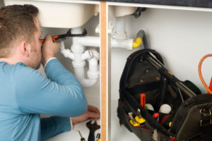 plumber fixing pipes under sink