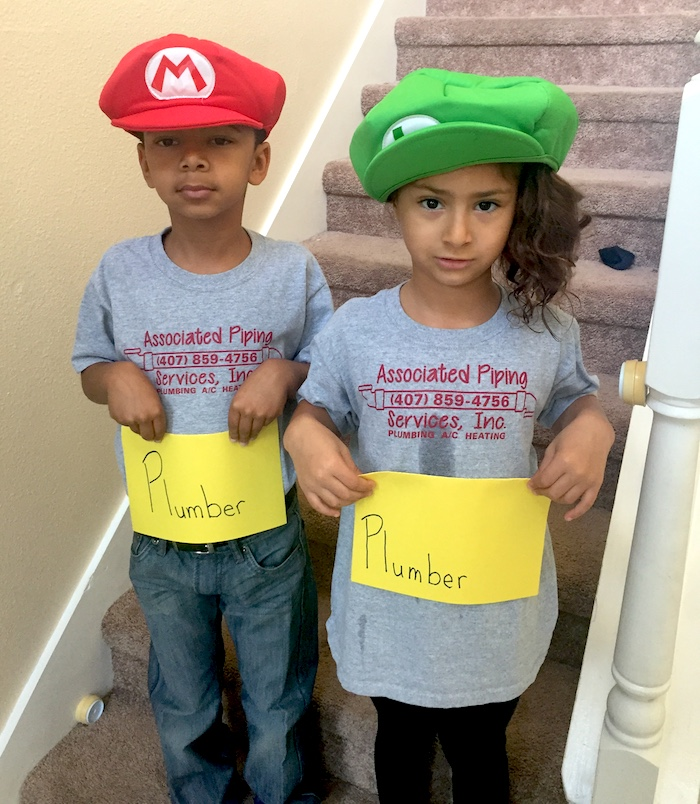 kids in mario and luigi hats holding plumber sign